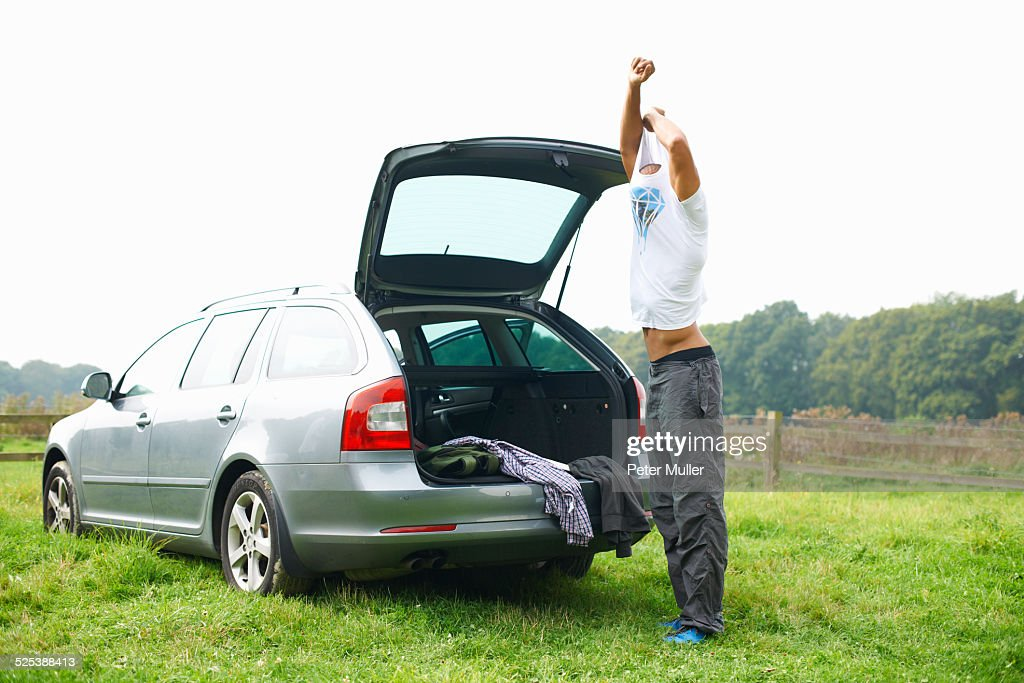 Man at rear of car changing clothes : Stock Photo