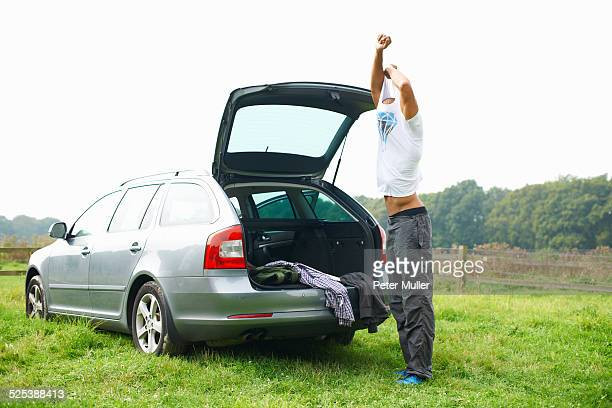 Man at rear of car changing clothes