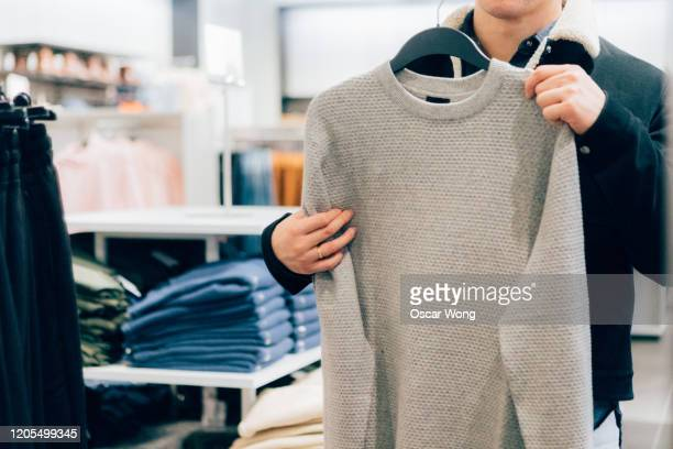 man at retail store holding a cardigan sweater looking at mirror - merchandise stock pictures, royalty-free photos & images