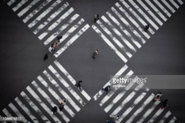 man at scramble crossing looking up to the sky - strisce pedonali foto e immagini stock