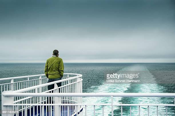 man at ship's stern, looking at horizon - heck stock-fotos und bilder