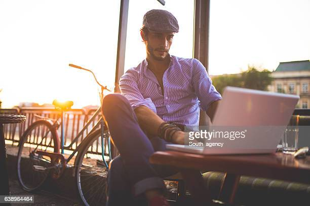 man at sidewalk cafe reading emails - south_agency stock pictures, royalty-free photos & images