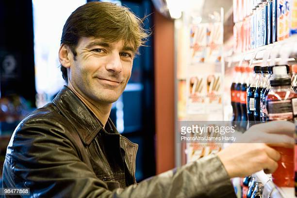 man at soft drink cooler in convenience store - energy drink stock pictures, royalty-free photos & images