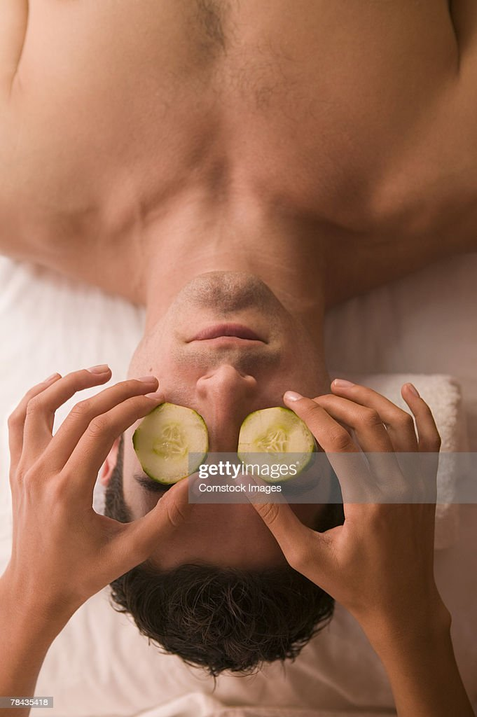 Man at spa with cucumber slices covering eyes : Stockfoto