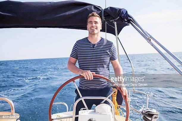 Man at steering wheel of sailship