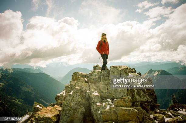 man at summit of pinnacle peak,mt rainier national park, washington state, usa - pinnacle peak stock-fotos und bilder