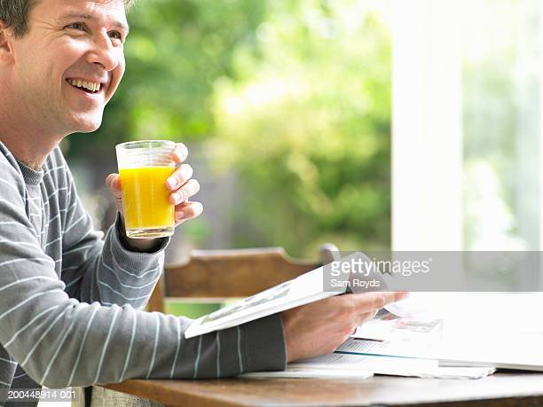 Man at table holding glass of orange juice and brochure, smiling