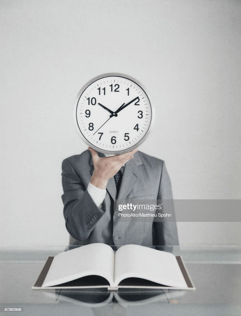 Man at table in suit holding clock in front of head, open book on table : Stock Photo