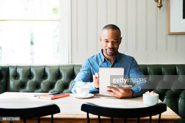 man at table with tablet - digital tablet stock pictures, royalty-free photos & images