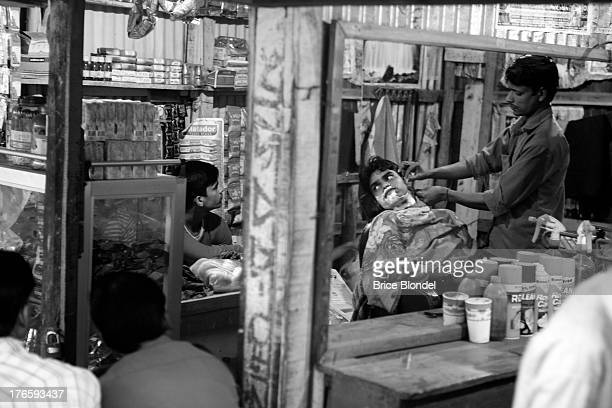 CONTENT] A man at the barber next to a small shop where people are watching a sports game on the television