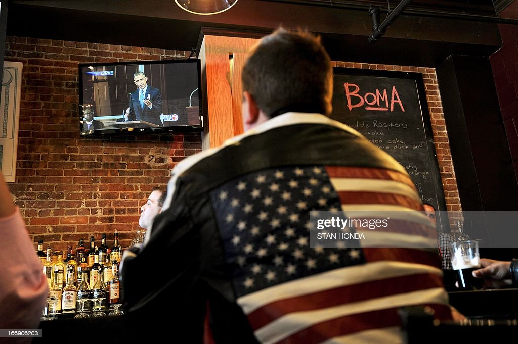 A man at the BoMA restaurant across the street from the Cathedral of the Holy Cross watches US President Barack Obama on television speak at the cathedral where an interfaith prayer service to honor the victims of the Boston Marathon bombings was being held April 18, 2013 in the South End neighborhood of Boston, Massachusetts.