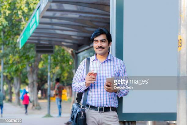 man at the bus stop- stock images - india politics stock pictures, royalty-free photos & images