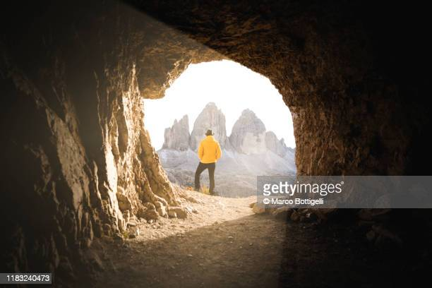 man at the end of tunnel admiring the three peaks of lavaredo, italy - speleology stock pictures, royalty-free photos & images