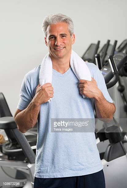 Man at the gym standing with towel around his neck