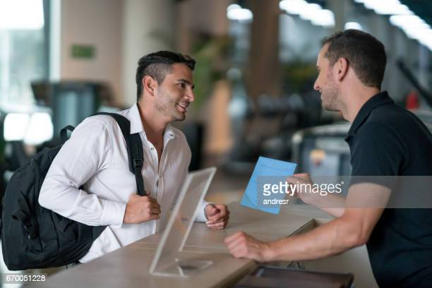 Man at the gym talking to receptionist about membership plans