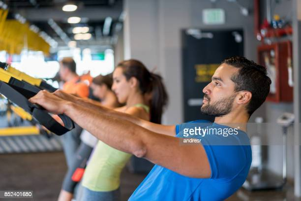 Man at the gym trying a suspension training class