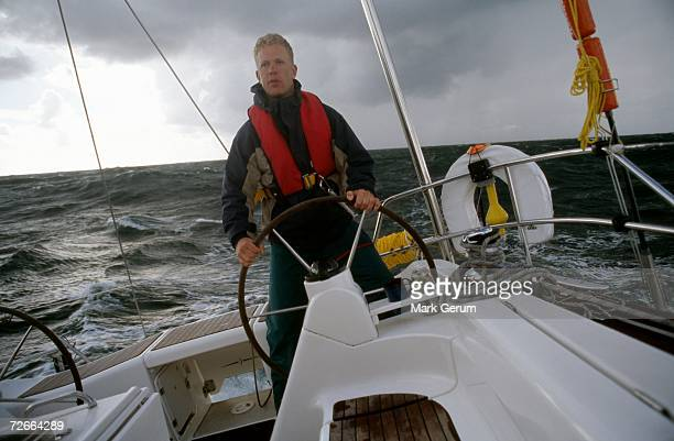 Man at the helm of yacht
