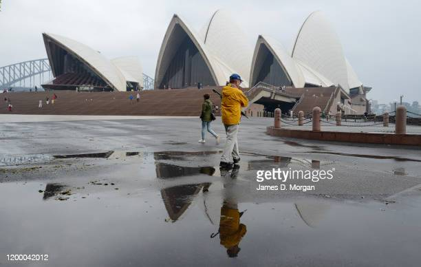 A man at the Opera House holds his umbrella on January 17 2020 in Sydney Australia A severe thunderstorm warning has been issued for some parts of...