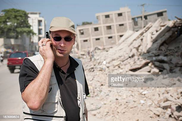 Man at the phone with collapsed building in background