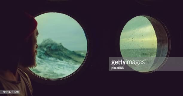 man at the porthole window of a vessel in a rough sea - porthole stock photos and pictures