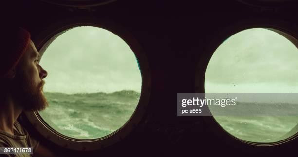 Mann am Bullauge Fenster eines Schiffes in rauer See