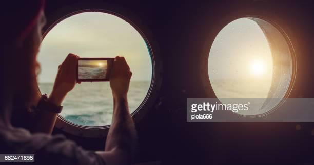 mann am bullauge fenster eines schiffes in rauer see - passagier wasserfahrzeug stock-fotos und bilder