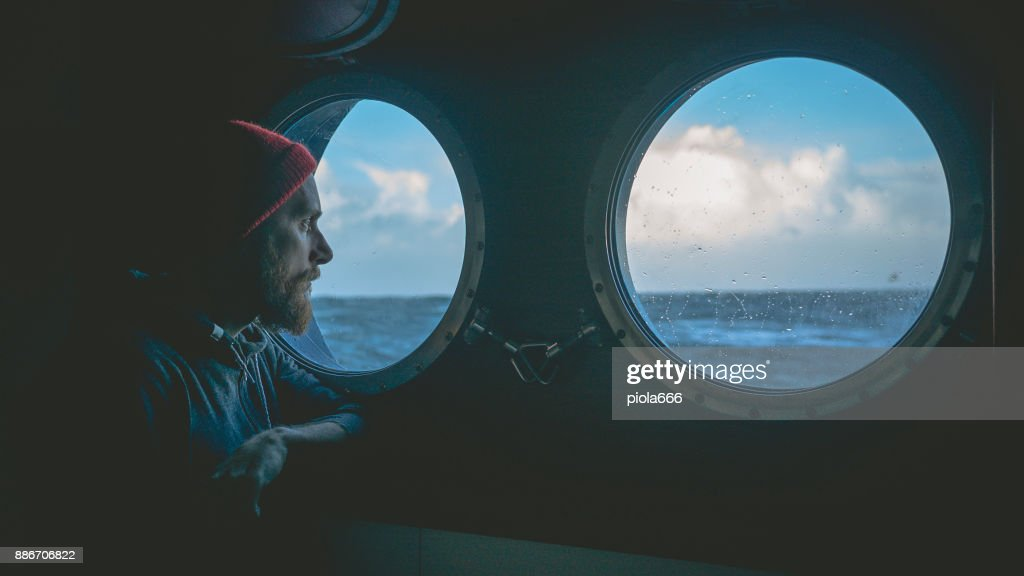 Man at the porthole window of a vessel in a rough sea : Stock Photo