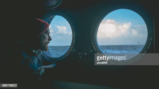 man at the porthole window of a vessel in a rough sea - boat stock pictures, royalty-free photos & images