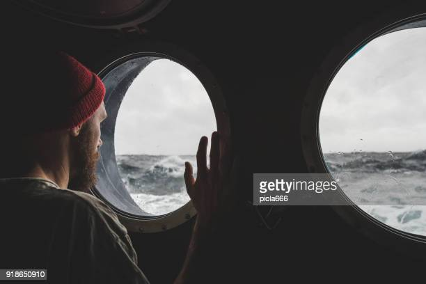 man at the porthole window of a vessel in a rough sea - tempesta foto e immagini stock