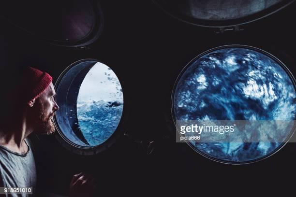man op de patrijspoort venster van een vaartuig in een ruwe zee - storm stockfoto's en -beelden