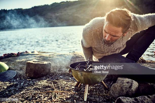 man at the riverside having a barbecue - simple living stock pictures, royalty-free photos & images