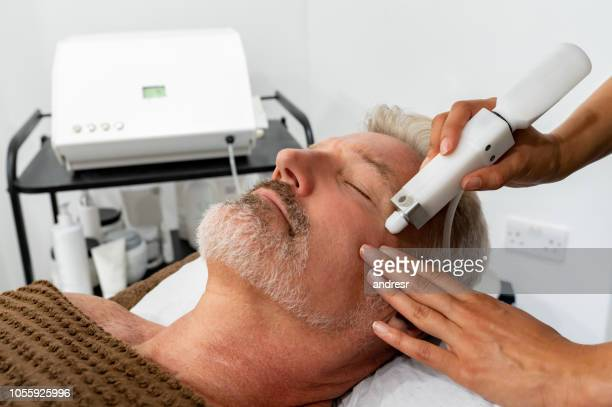 man at the spa getting a facial laser treatment - laser stock pictures, royalty-free photos & images