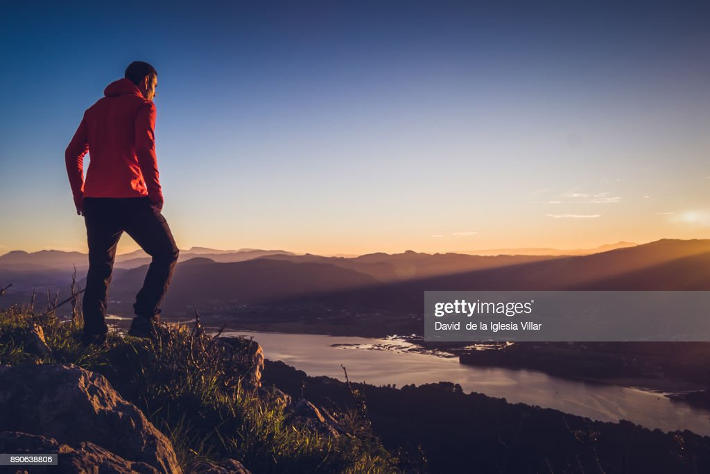 A man at the top of a mountain at sunrise : Photo