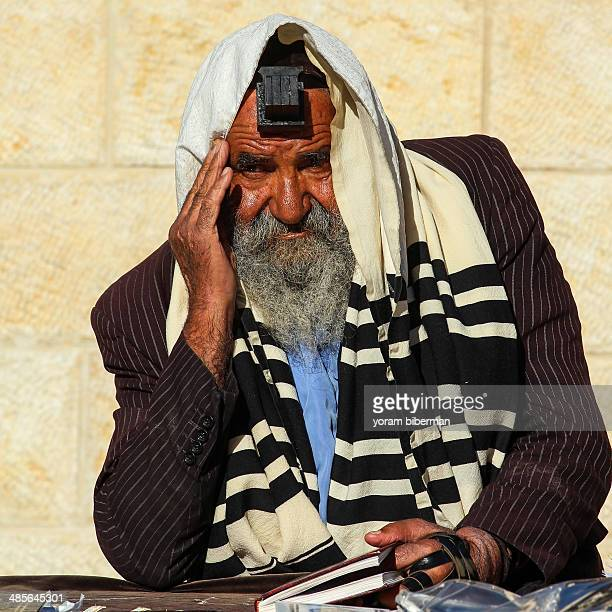 CONTENT] A man at the Western Wall with his forehead and hand Tefillin looking forward