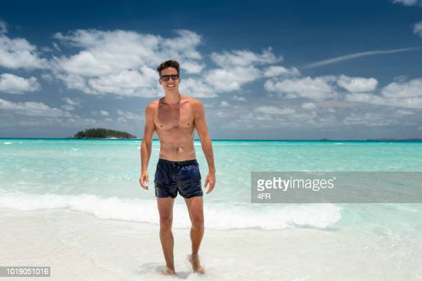 man at the white sand beach, whitsunday islands, queensland, australia - swimwear stock pictures, royalty-free photos & images