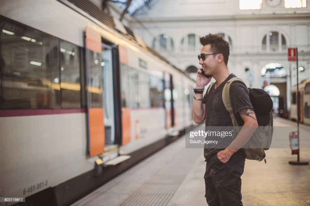 Man at train station using phone : Stock Photo