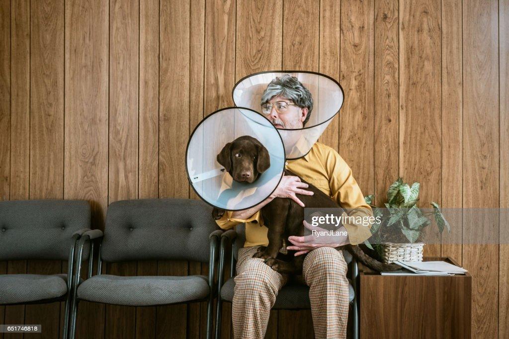 Man at Veterinarian Wearing Dog Cone : Stock Photo