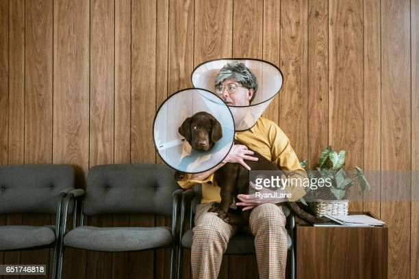 man at veterinarian wearing dog cone - elizabethan collar stock photos and pictures