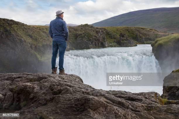 mann am wasserfall in island - umkehrer stock-fotos und bilder