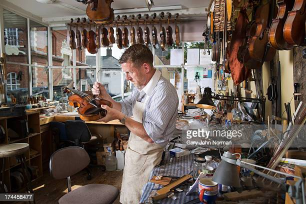 man at work in violin shop - violin stock pictures, royalty-free photos & images