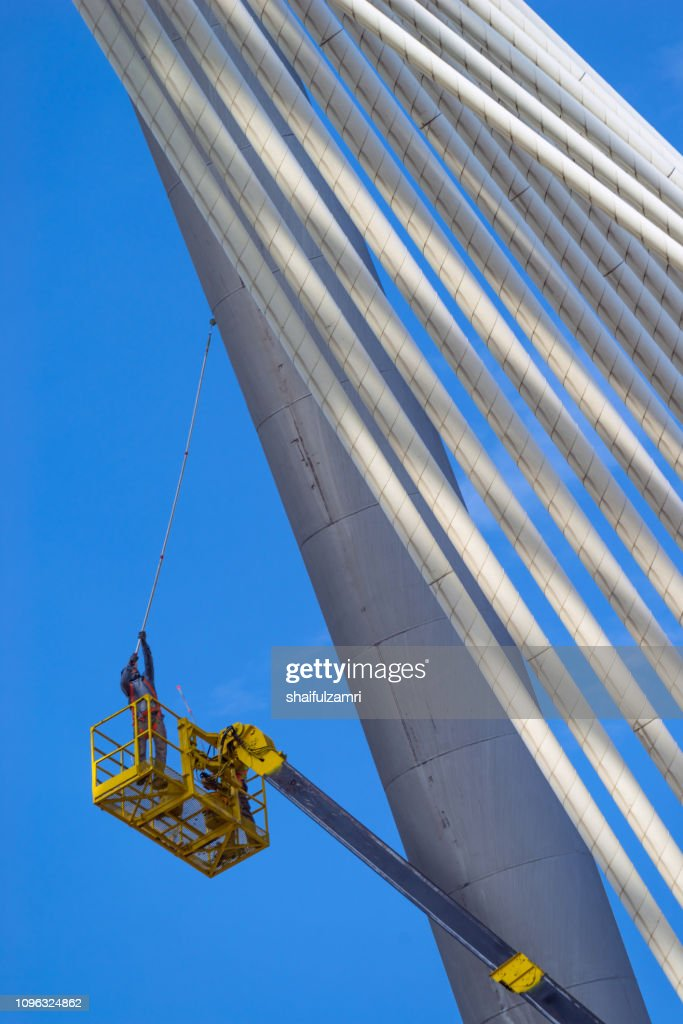 Man at work, paints suspension bridge for maintenance. : Stock Photo