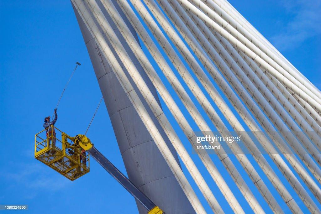 Man at work, paints suspension bridge for maintenance. : Stock Photo