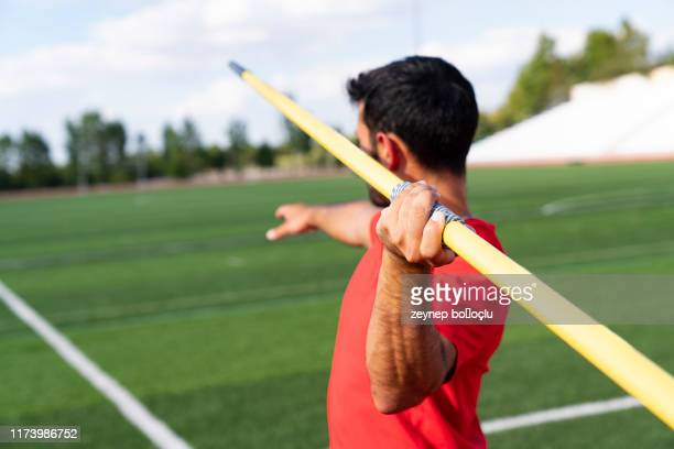man athlete about to throw a javelin in the stadium. - men's field event stock pictures, royalty-free photos & images