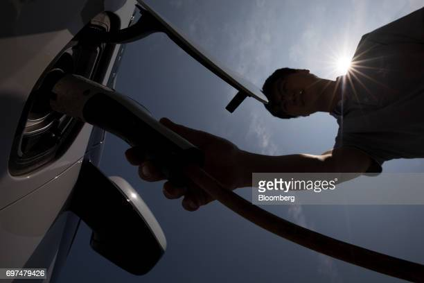 A man attaches a charging plug to a General Motors Co Chevrolet 2017 Volt hybrid electric vehicle at a charging station in Jeju South Korea on...