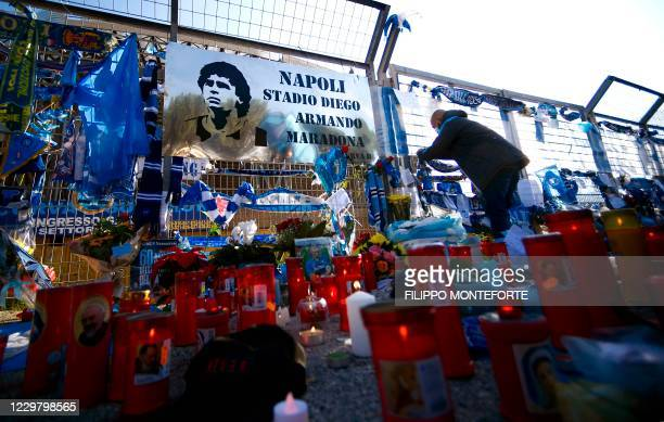 Man attaches a scarf at a makeshift altar dedicated to the memory of late Argentinian football legend Diego Maradona, next to a board rechristening...