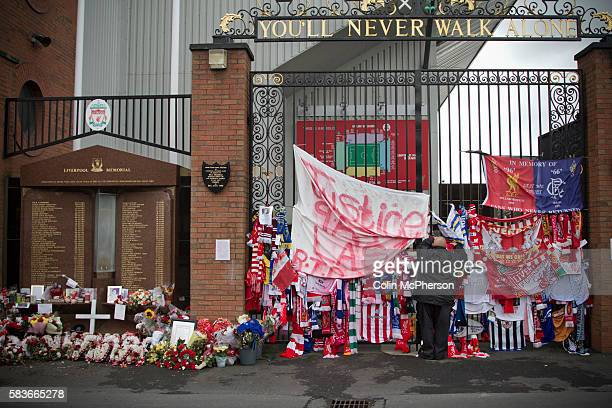 A man attaching a scarf to the Shankly Gates next to the memorial at Anfield to the 1989 Hillsborough stadium disaster where 96 Liverpool football...