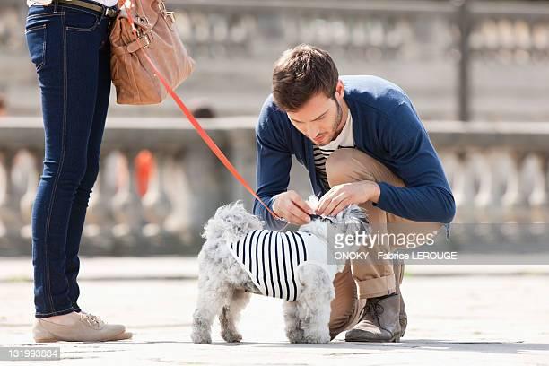 Man attaching leash on a puppy, Paris, Ile-de-France, France