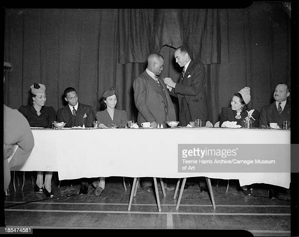 Man attaching pin on Bill 'Bojangles' Robinson's lapel, with two men and three women seated at banquet table looking on, for YMCA Emblem club...