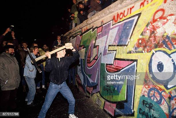 A man attacks the Berlin Wall with a pickaxe on the night of November 9th 1989 as news spread rapidly that the East German Government would now start...