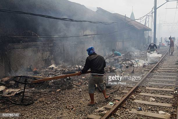 A man attempt to put out a fire in a slum area next to railway tracks in Kampung Bandan Fire destroyed approximately 100 wooden dwellings built along...